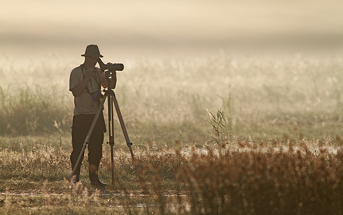 Lintuharrastaja katsoo Yyterin lietteillä lintuja kaukoputkella